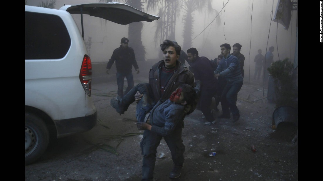 An injured boy is carried following reported airstrikes in the Syrian town of Hamouria on Wednesday, December 9. The Syrian Observatory for Human Rights reported at least 11 civilians, including four children, were killed in strikes, but it was unclear who was responsible.