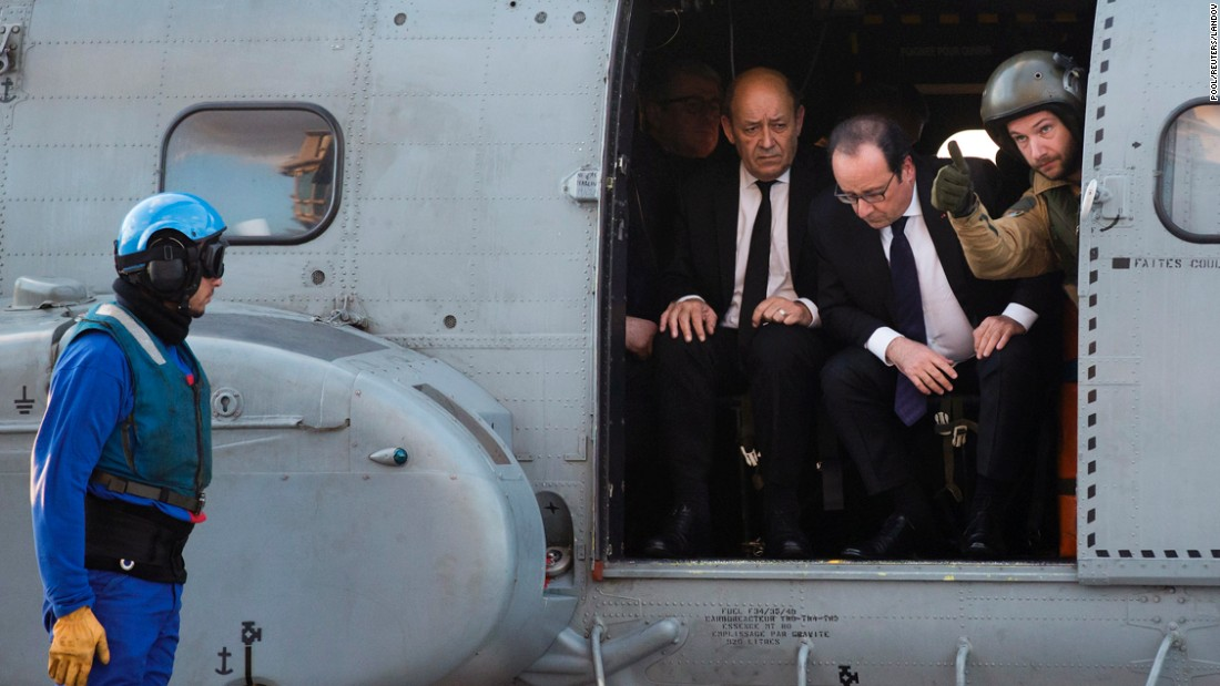 French President Francois Hollande, second from right, and French Defense Minister Jean-Yves Le Drian arrive by helicopter to the Charles de Gaulle aircraft carrier on Friday, December 4. The vessel is the Mediterranean Sea to help fight the ISIS militant group.