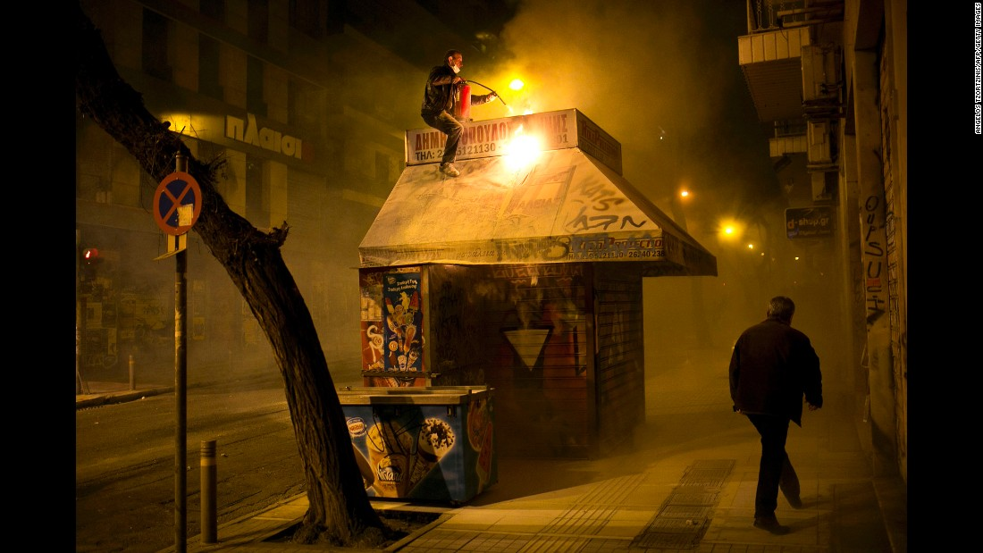 A vendor tries to put out a fire at his kiosk during clashes between riot police and protesters in Athens, Greece, on Sunday, December 6. Part of central Athens was turned into a battleground during a march to mark the seventh anniversary of Alexis Grigoropoulos' death. Grigoropoulos, 15, was fatally shot by police in 2008.