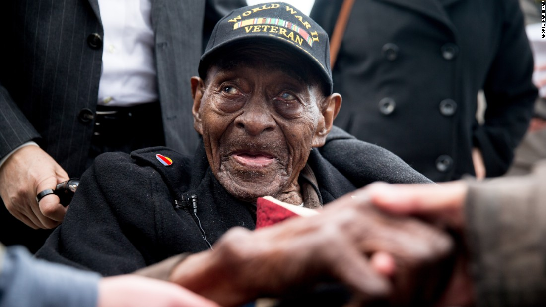 Frank Levingston Jr., who at 110 years old is believed to be the United States' oldest military veteran, is greeted after a wreath-laying ceremony at the World War II Memorial in Washington on Monday, December 7. Levingston is a D-Day veteran who survived the Pearl Harbor attacks that took place 74 years ago.