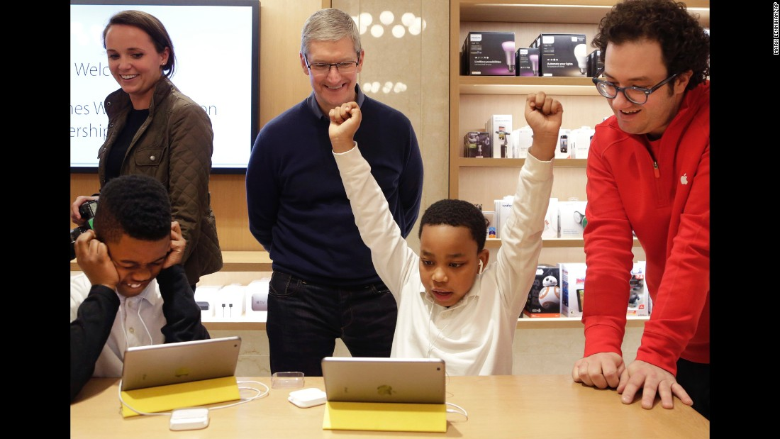 "Jaysean Erby raises his arms in front of Apple CEO Tim Cook as he solves a coding problem Wednesday, December 9, at an Apple Store in New York. Third-graders were invited to the store to play a ""Star Wars"" game hosted on code.org. Apple is hosting Hour of Code events around the world as part of Computer Science Education Week."