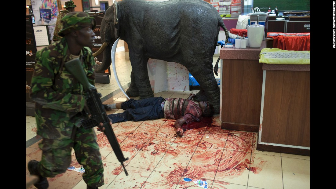 A soldier walks by a body while searching for gunmen at Westgate Mall in Nairobi, Kenya, on September 21, 2013. A group of armed men attacked the upscale shopping center, killing at least 20 people and wounding more than 50. Tyler Hicks won the Pulitzer for capturing this image.  Hicks used a Canon camera with various lenses and exposures.