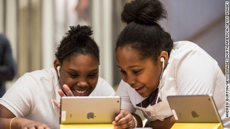 "NEW YORK, NY - DECEMBER 09:  Jiavaennye Green (L) and Taylor Phillips, third grade children from PS 57 James Weldon Johnson Leadership Academy, learn how to code at an Apple Store through Apple's ""Hour of Code"" workshop program on December 9, 2015 in New York City. Tim Cook, CEO of Apple, visited the students and said he hoped that teaching coding to children would become standard in education throughout the United States.  (Photo by Andrew Burton/Getty Images)"