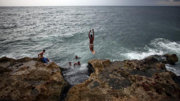 Locals swim along the Malecon coastal area in Havana.