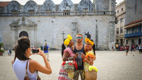 A U.S. tourist poses for a snapshot between two Cubans clad in vibrant attire in Old Havana.