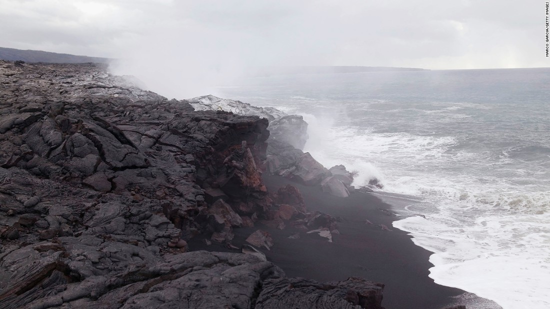 Steam and poisonous gas rise and lava flows into the ocean from Kilauea volcano at Hawaii Volcanoes National Park.