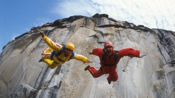 """Carl Boenish and his wife, Jean, leap from a cliff in the early days of BASE jumping, an extreme sport in which participants jump from fixed objects and use parachutes to slow their falls. Carl Boenish is considered the """"father"""" of BASE jumping, and his amazing life story is the subject of CNN Films' """"Sunshine Superman."""""""