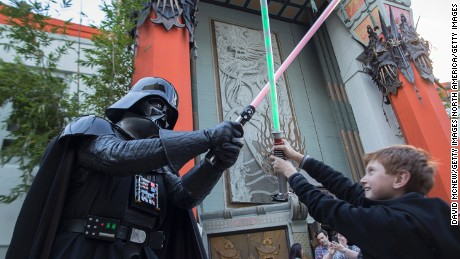 "LOS ANGELES, CA - DECEMBER 12:  A boy engages David Baxter, who is dressed as Darth Vader, in a light saber battle as fans camp out in the TLC Chinese Theatre courtyard for the premiere of Walt Disney Pictures And Lucasfilm's ""Star Wars: The Force Awakens"" on December 12, 2015 in the Hollywood section of Los Angeles, California.  (Photo by David McNew/Getty Images)"