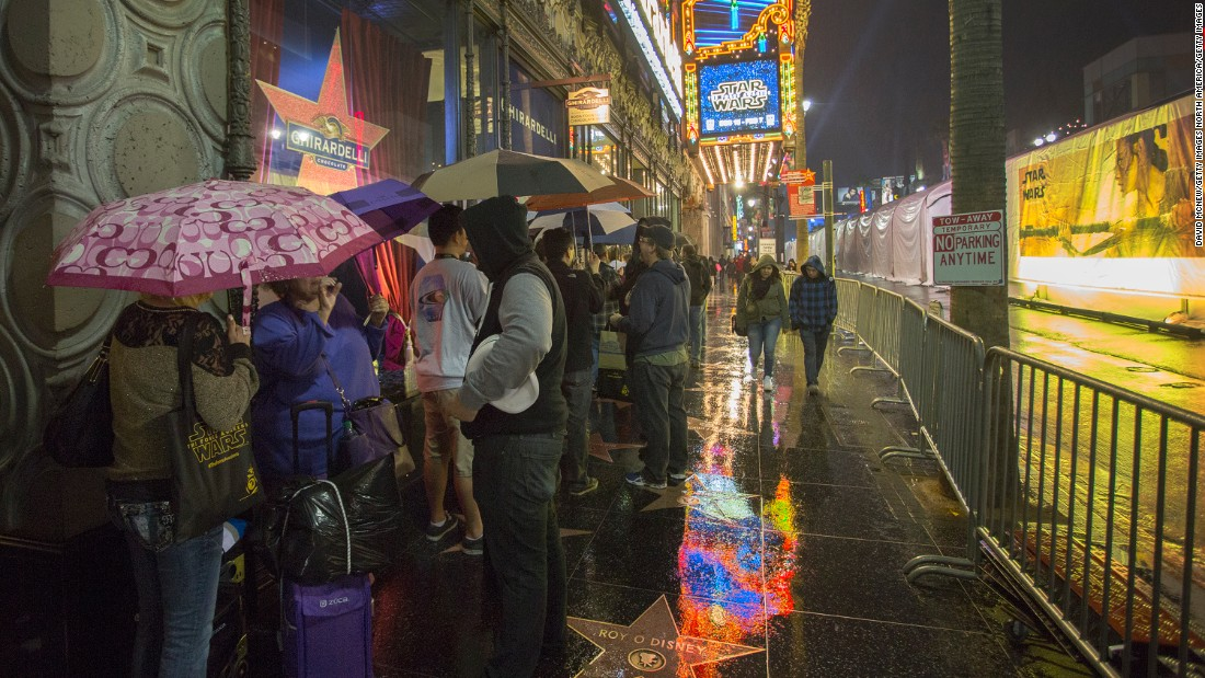People stand in line in the rain outside of the Disney Studio Store next to the El Capitan Theatre, where blocks-long tenting has been set up for the premiere.