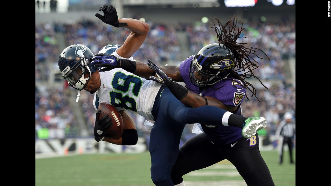 Seattle wide receiver Doug Baldwin, left, is hit by Baltimore's Kendrick Lewis during an NFL game in Seattle on Sunday, December 13. Baldwin scored on the play -- one of three touchdowns he had in the 35-6 drubbing.