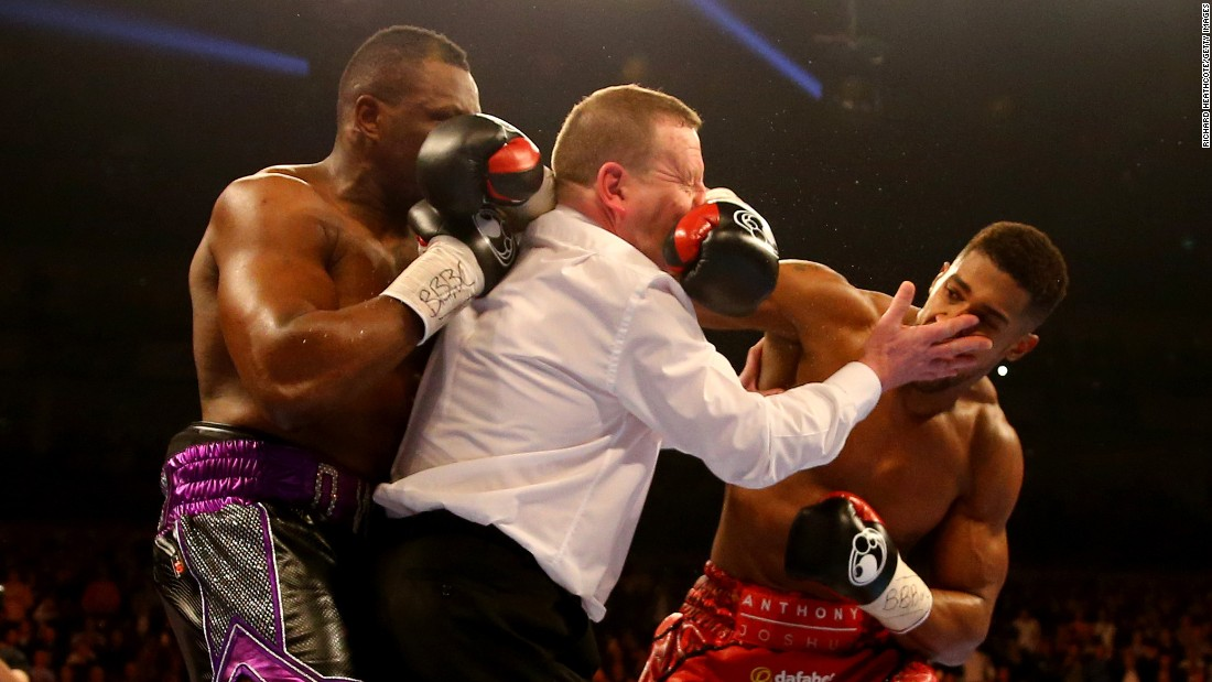 Anthony Joshua, right, throws a punch after the end of the first round Saturday, December 12, in London. Joshua stopped Dillian Whyte in the seventh round to win the British heavyweight title and improve his record to 15-0.