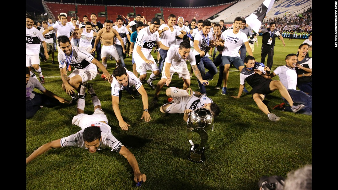 Olimpia players celebrate Wednesday, December 9, after defeating Cerro Porteno to win the Apertura playoff final in Asuncion, Paraguay.