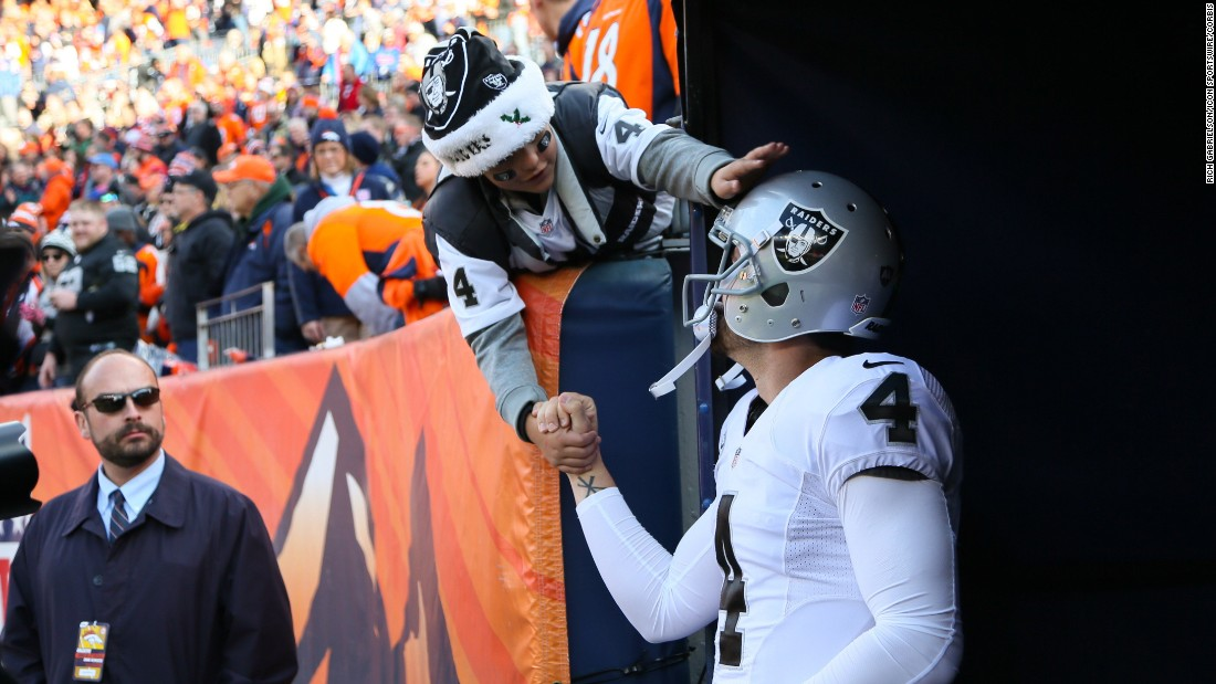 A fan reaches out to Oakland quarterback Derek Carr before an NFL game in Denver on Sunday, December 13.