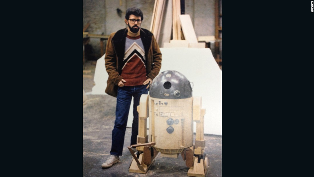 "George Lucas stands next to a prototype of R2-D2, the plucky droid that harbored plans for the Death Star. Lucas and Roger Christian played with a variety of models before settling on one that would fit actor Kenny Baker and all the electronics required to move the robot around. It was cramped and hot, and the shoot was testing at times, especially in Tunisia. Christian says R2 often failed to work, and on the opening day of filming struggled to stay upright, resulting in most of the footage being cut from the final version of ""A New Hope."""
