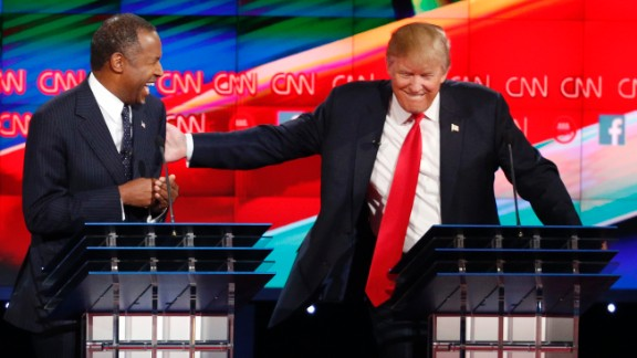 Carson and Trump share a laugh on stage.