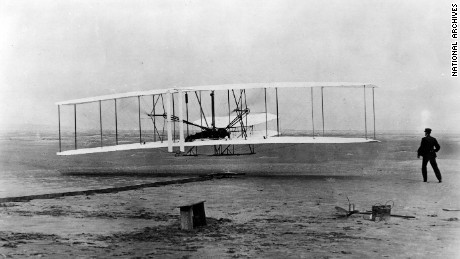 """Original Wright Brothers 1903 Aeroplane (""Kitty Hawk"") in first flight, December 17, 1903, at Kitty Hawk, NC. Orville Wright at controls. Wilbur Wright at right (First flight was 12 seconds)"" By Orville Wright and John T. Daniels, December 17, 1903 National Archives and Records Administration, Records of the War Department General and Special Staffs (165-WW-713-6) [VENDOR # 16]"