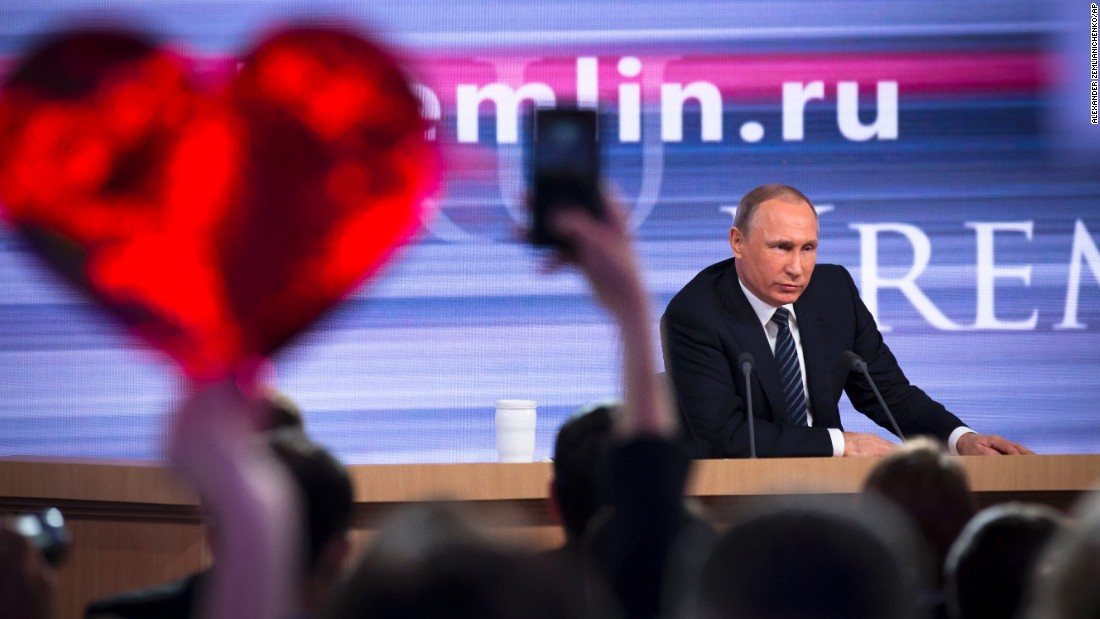 A reporter holds up a heart-shaped poster to attract the attention of Russian President Vladimir Putin during Putin's end-of-the-year news conference on Thursday, December 17.