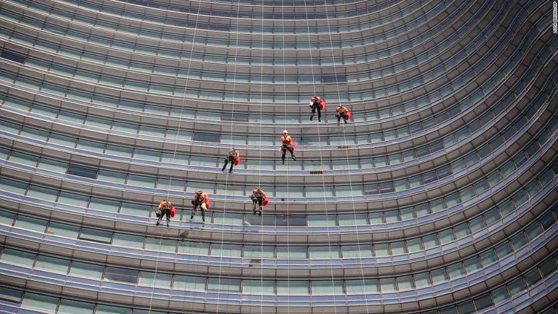 Window cleaners work at the UniCredit Tower, a skyscraper in Milan, Italy, on Friday, December 11.