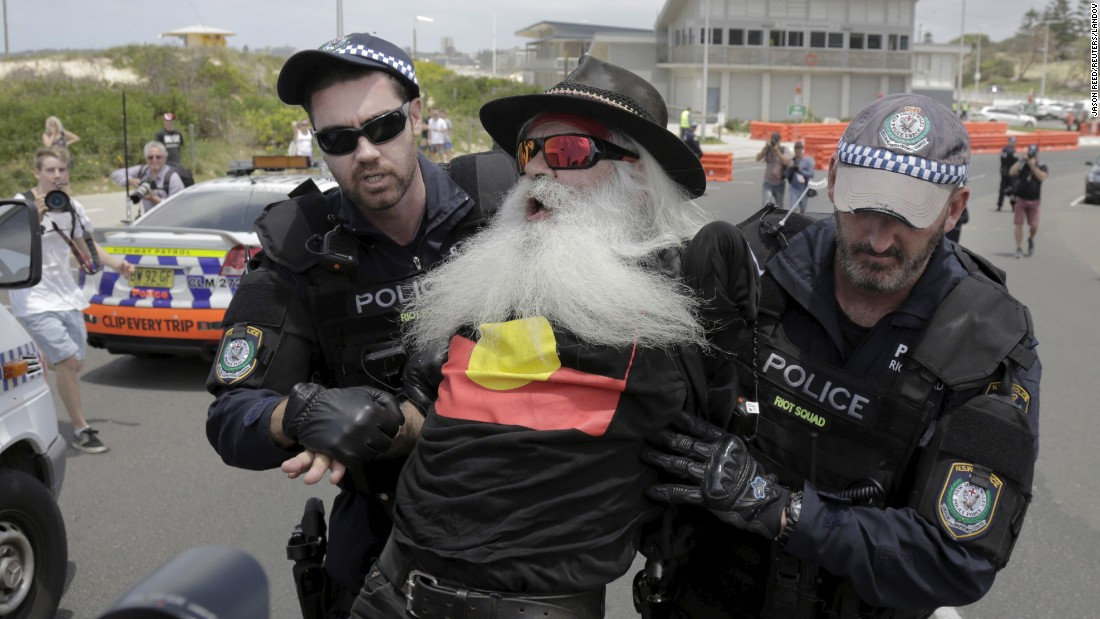 A protester is detained by police Saturday, December 12, during demonstrations held on the 10th anniversary of race riots in Sydney.