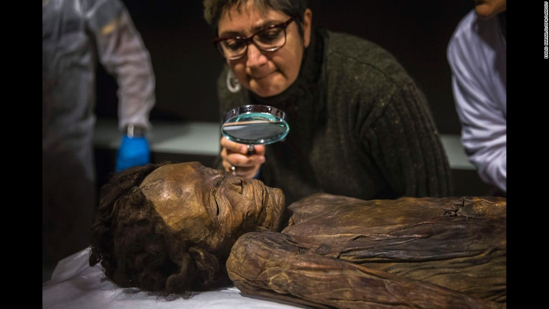 "An archaeologist in Madrid observes the ""Guanche Mummy of Barranco de Herques"" upon its arrival at the National Museum of Archeology on Monday, December 14. The 18th-century mummy is from Tenerife in Spain's Canary Islands."