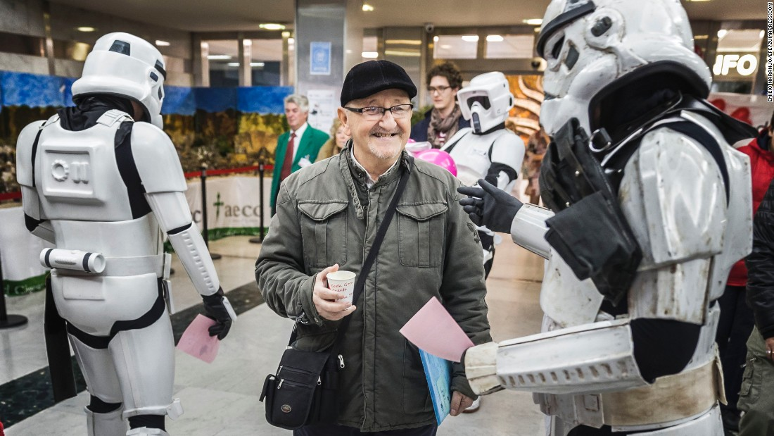 "A person dressed as a ""Star Wars"" Stormtrooper informs a man about a blood drive taking place at a Madrid hospital on Tuesday, December 15."
