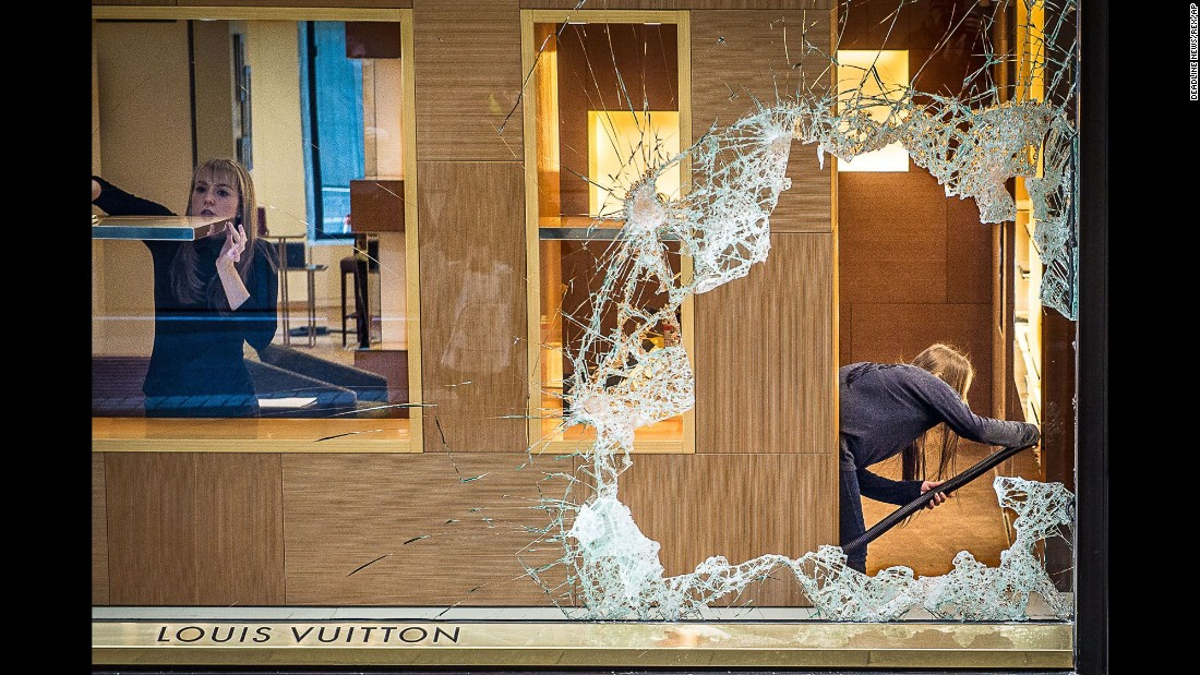Staff members clean up Thursday, December 17, after an apparent burglary at a Louis Vuitton store in Edinburgh, Scotland.