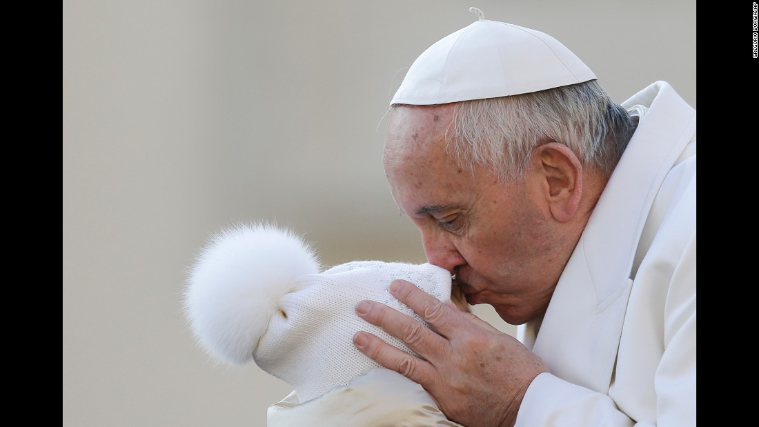 Pope Francis kisses a child at the Vatican on Wednesday, December 16.