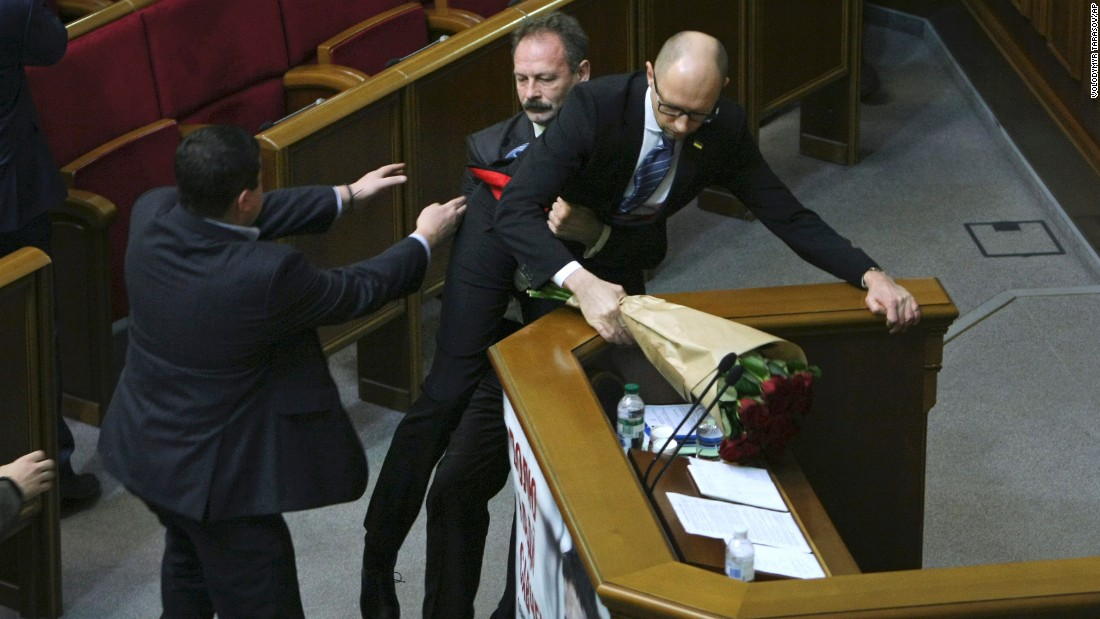 "Ukrainian lawmaker Oleh Barna, second left, pulls Ukrainian Prime Minister Arseniy Yatsenuk out from the podium during his speech in Parliament on Friday, December 11. Barna's interruption started a fight among lawmakers, <a href=""http://www.kyivpost.com/article/content/kyiv-post-plus/yatsenyuk-denies-responsibility-for-corruption-gets-attacked-by-lawmaker-403982.html"" target=""_blank"">according to the Kiev Post.</a>"