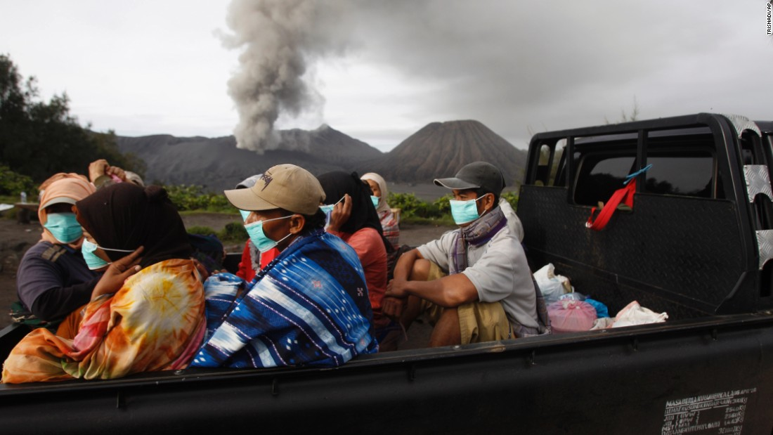 Villagers ride in the back of a truck as Mount Bromo spews volcanic material in Probolinggo, Indonesia, on Tuesday, December 15.