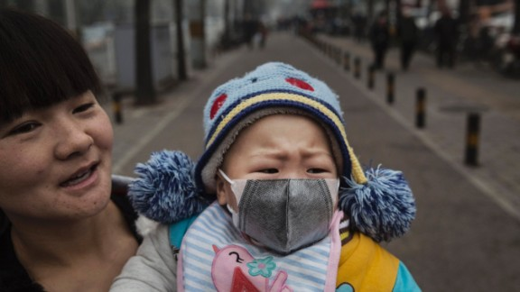 """A Chinese infant wears a mask in Beijing, which was on """"red alert"""" for heavy pollution, in 2015."""