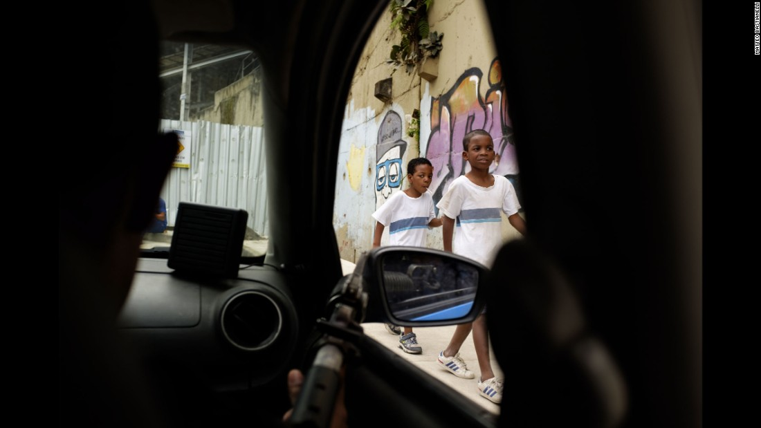 "Two children walk past a police checkpoint in Rio de Janeiro. While visiting the city's infamous favelas, photographer Matteo Bastianelli explored the complex relationship between some of Rio's poorest residents and the state's security forces. He's titled his project ""Suppressed Favelas."""