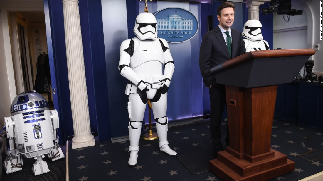 "White House press secretary Josh Earnest speaks in the briefing room on December 18, with ""Star Wars"" characters R2-D2 and Storm Troopers."