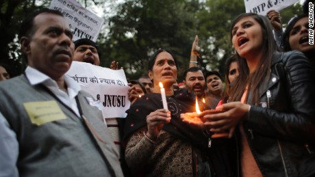 Father, left and mother, center of the Indian student victim who was fatally gang raped three years ago join others at a candle lit vigil in New Delhi, India, on Wednesday, December 16.