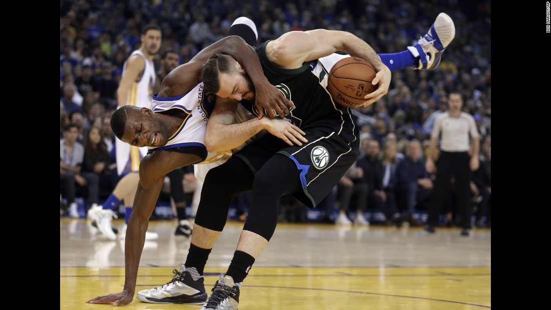 Golden State Warriors' Festus Ezeli, left, fouls Milwaukee Bucks' Miles Plumlee during the first quarter of an NBA basketball game Friday, December 18, in Oakland, California.