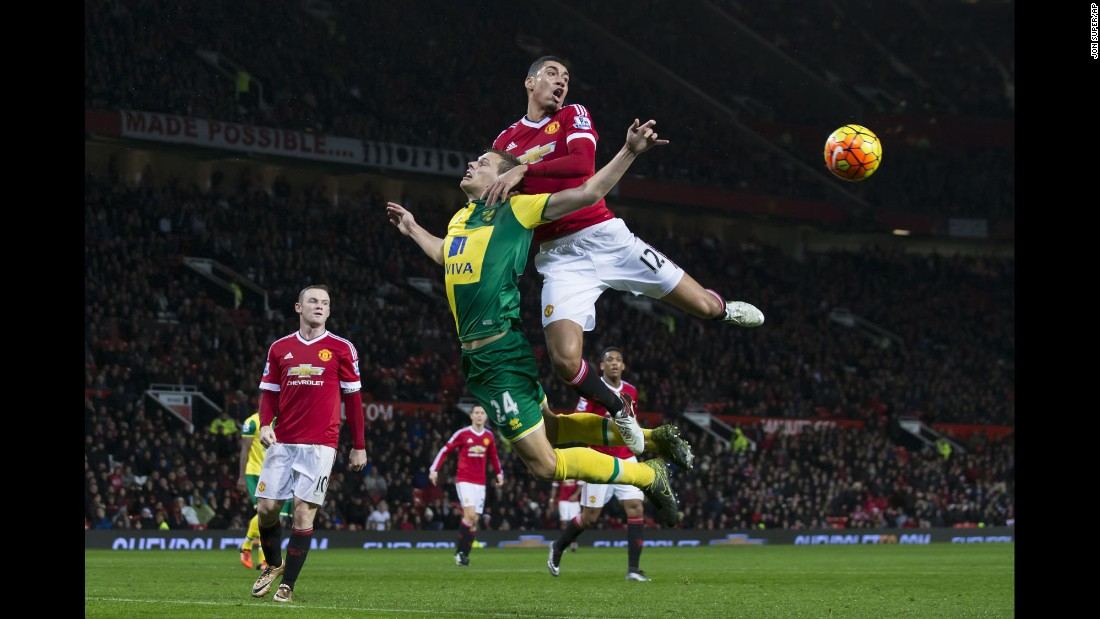 Manchester United's Chris Smalling, top, fights for the ball against Norwich City's Ryan Bennett during an English Premier League soccer match at Old Trafford Stadium in Manchester on Friday, December 19.