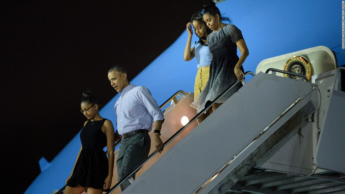 Sasha Obama, from left, President Barack Obama, Malia Obama and first lady Michelle Obama arrive at Hickam Air Force Base in Honolulu on Saturday, December 19.