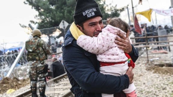 A man carrying a baby cries after crossing the Greek-Macedonian border with other migrants and refugees, near the town of Gevgelija, on December 4, 2015.