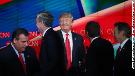 Republican presidential candidate Donald Trump smiles (C) as New Jersey Gov. Chris Christie (L), Jeb Bush (2ndL), Ohio Gov. John Kasich (2nd R) and U.S. Sen. Rand Paul (R-KY) walk onstage afterthe CNN Republican presidential debate on December 15, 2015 in Las Vegas, Nevada. This is the last GOP debate of the year, with U.S. Sen. Ted Cruz (R-TX) gaining in the polls in Iowa and other early voting states and Donald Trump rising in national polls.