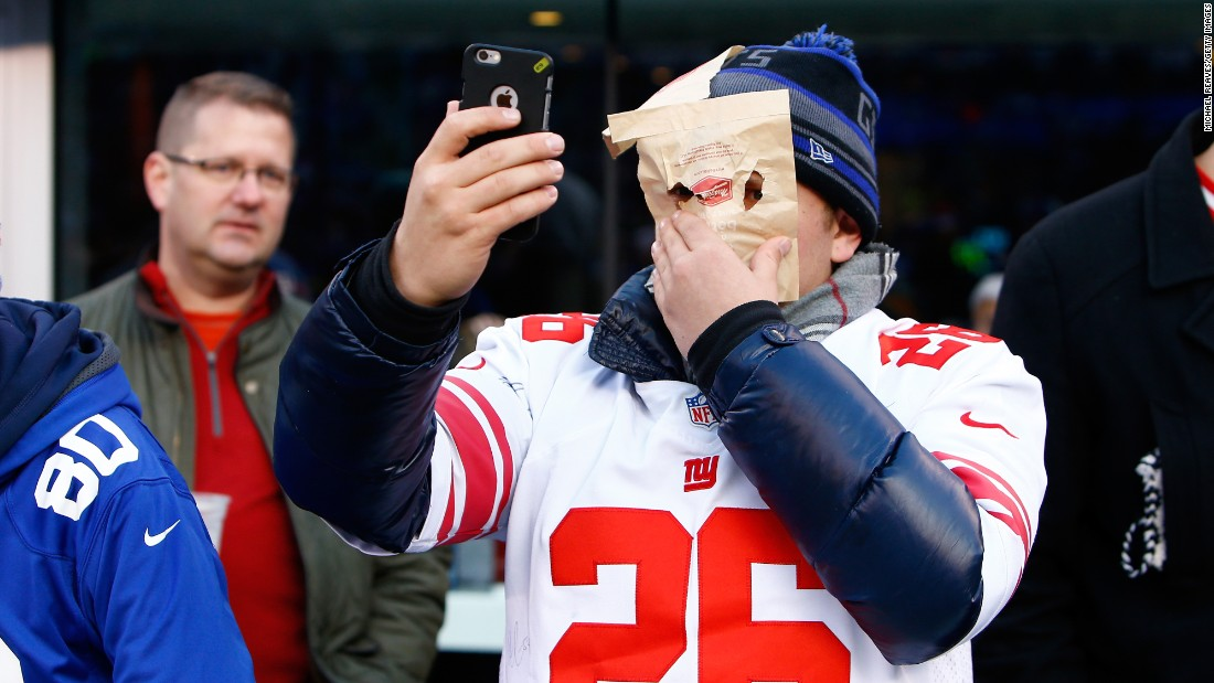 A New York Giants fan takes a selfie with a paper bag over his face during the game between the Carolina Panthers and the New York Giants at MetLife Stadium in East Rutherford, New Jersey, on Sunday, December 20.