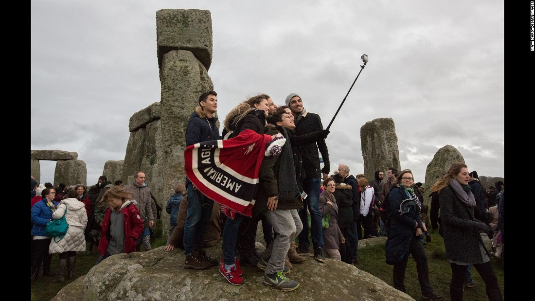 People gather to take a selfie as pagans and revelers gather at Stonehenge in Wiltshire, England, as they take part in a winter solstice ceremony on Tuesday, December 22.