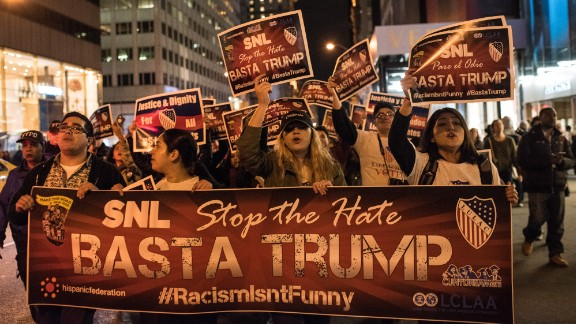 """Members of Latino organizations march from the Trump Tower to NBC studios in New York to protest Trump's """"Saturday Night Live"""" appearance on November 7."""