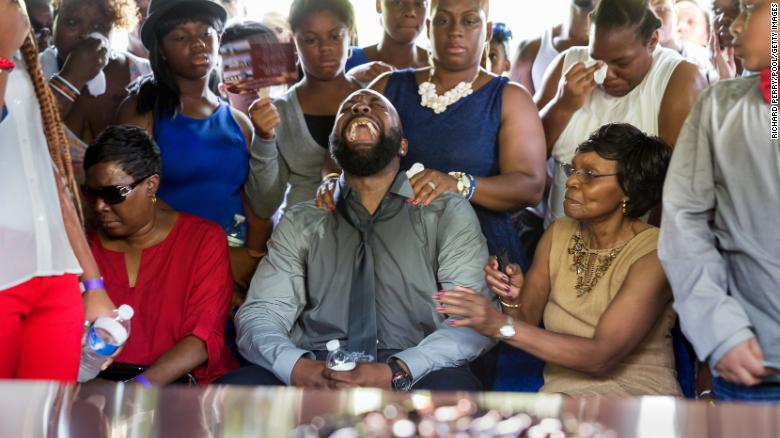 Michael Brown Sr. yells out as the casket of his son Michael is lowered into the ground during his funeral at St. Peters Cemetery in August 2014 in St. Louis.
