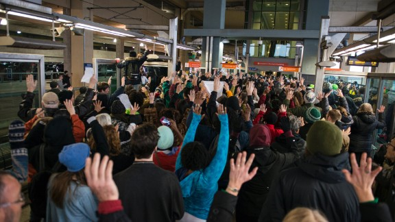 """Black Lives Matter protesters hold their hands in the air and chant, """"Hands up, don't shoot"""" at the Minneapolis-St. Paul International Airport light rail stop in Minneapolis on Wednesday, December 23."""
