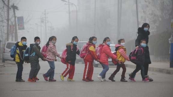 Schoolchildren wearing face masks walk across a street in Jinan, China, amid heavy air pollution in 2015.