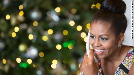 Michelle Obama smiles while talking to a child as part of the annual NORAD Tracks Santa program.