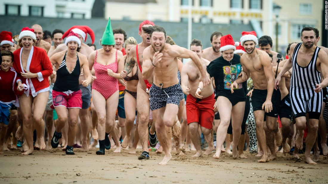 People run for the water at Exmouth Beach in Devon, England, during the Exmouth Christmas Day Swim on Friday, December 25.