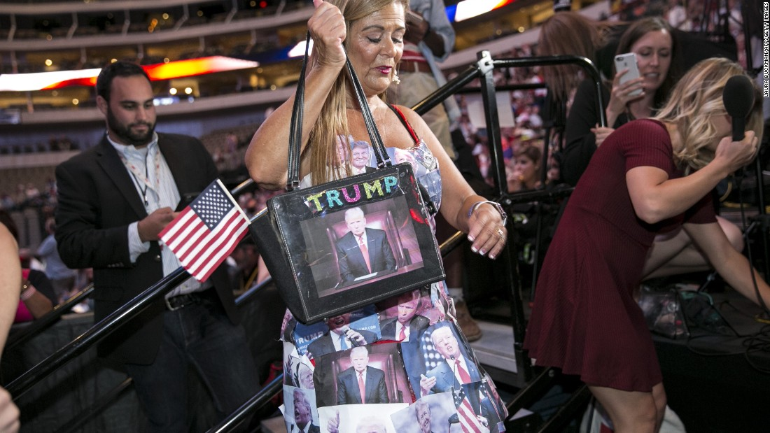 A woman wears a dress covered in printouts of Donald Trump's face during a campaign rally in Dallas on September 14.