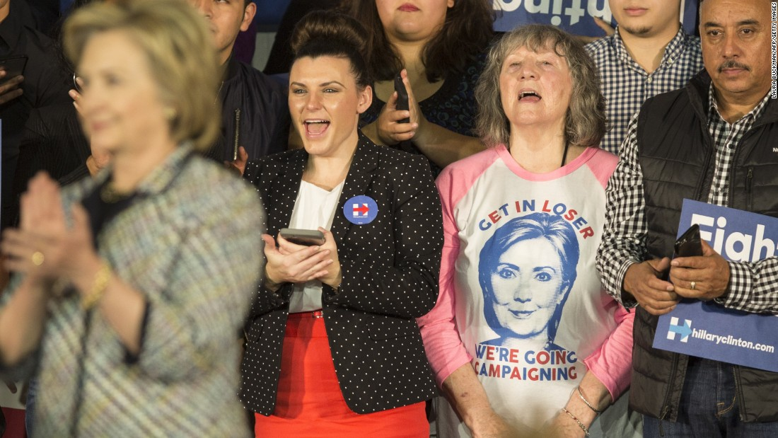 "A woman behind Hillary Clinton wears a ""Get in Loser, We're Going Campaigning"" shirt during an event in Dallas on November 17."