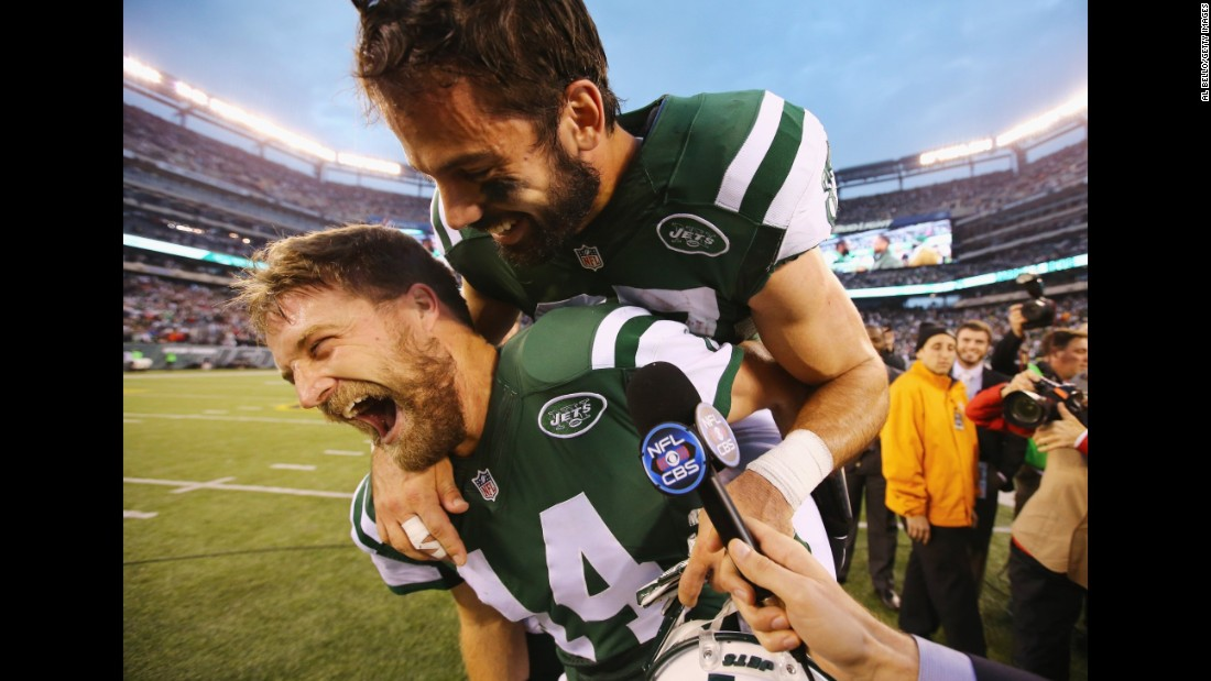 New York Jets wide receiver Eric Decker jumps on the back of quarterback Ryan Fitzpatrick during a television interview Sunday, December 27, in East Rutherford, New Jersey. The two teamed up for the game-winning touchdown as the Jets defeated the New England Patriots 26-20 in overtime.