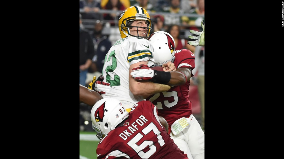 Green Bay quarterback Aaron Rodgers is sacked by Arizona's Alex Okafor and Jerraud Powers during an NFL game in Glendale, Arizona, on Sunday, December 27. Rodgers was sacked eight times as the Cardinals rolled to a 38-8 victory.